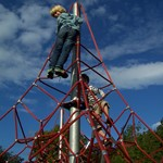 Boys on spiderweb climbing frame.JPG